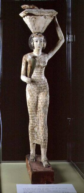 Female bearer of offerings carrying a water vase in her hand and a vessel on her head