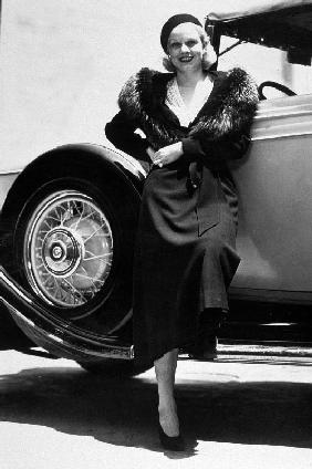 American Actress Jean Harlow posing near a car