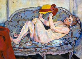 Lying female act on a chaise longue with hat in th